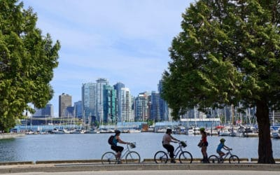 Cyclists on Vancouver Seawall with view of downtown Vancouver