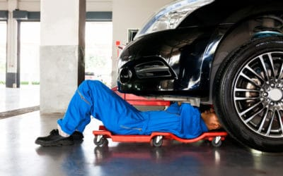 Mechanic working on car in garage