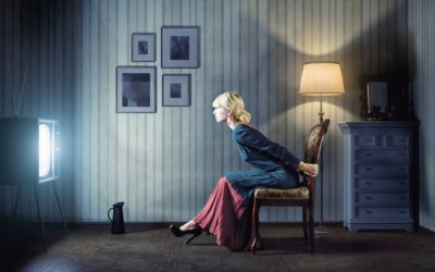 : A young woman sitting on a vintage chair and watching TV