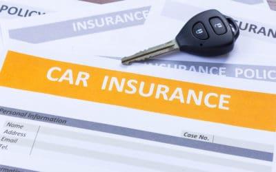 Car keys sitting atop a car insurance form