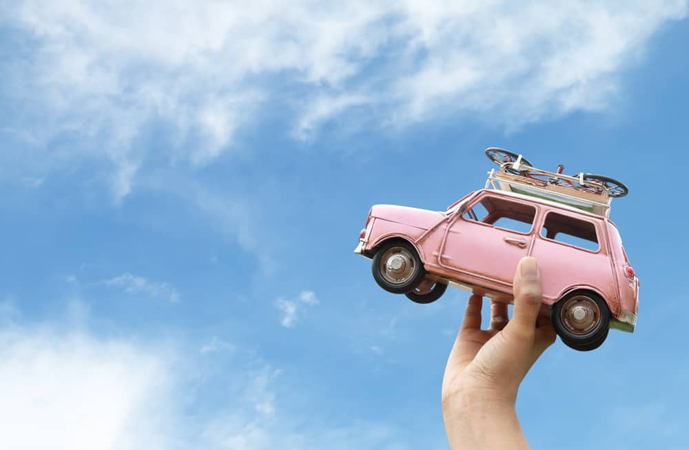 Tiny pink car in hand with blue sky in background