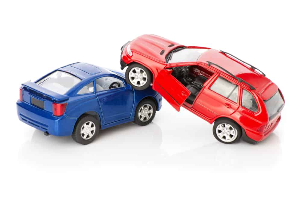 Collision of two toy cars against blank white background