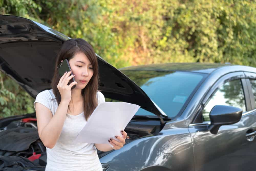 Woman talking on phone and looking at form in front of broken down car