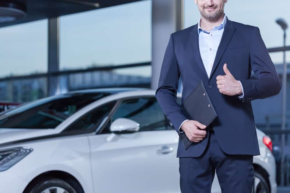 Man standing in front of car with thumbs up