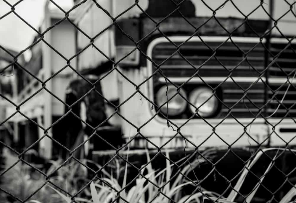 Black and white scene of a truck behind metal a wire fence