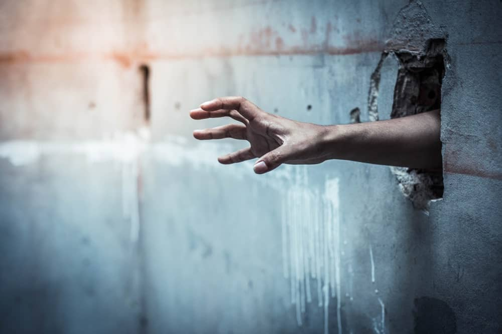 A man's hand reaching out of a hole in a prison wall