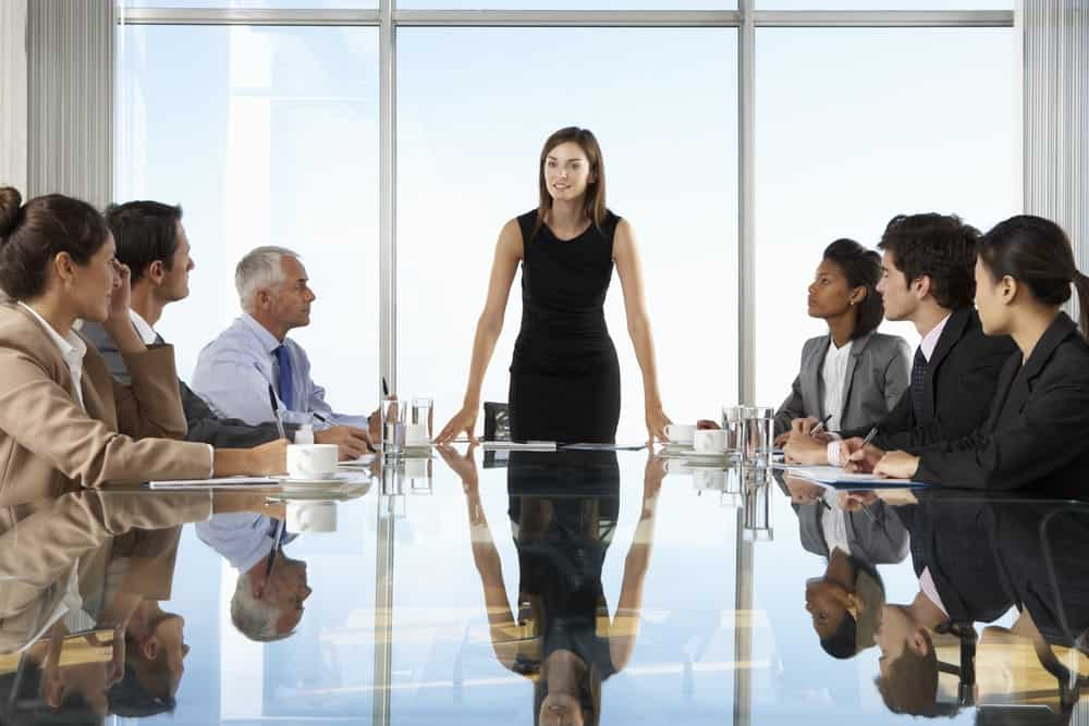 Chief Executive Officer standing in the middle of a business meeting.