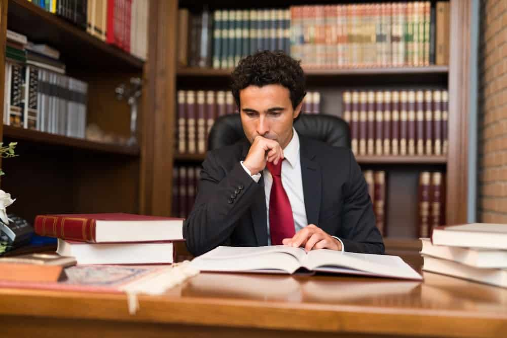 Man in suit reading a book in a law library.