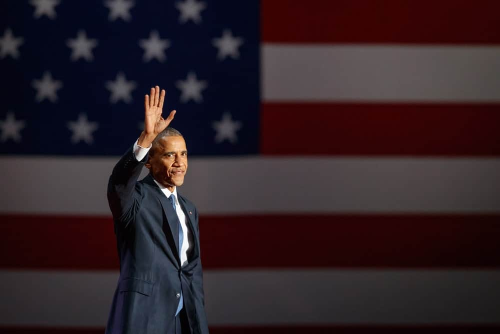 Barack Obama waving his hand with the USA flag as a backdrop.