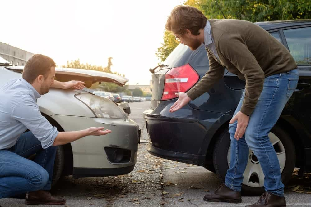 Two men arguing over a rear-car accident.