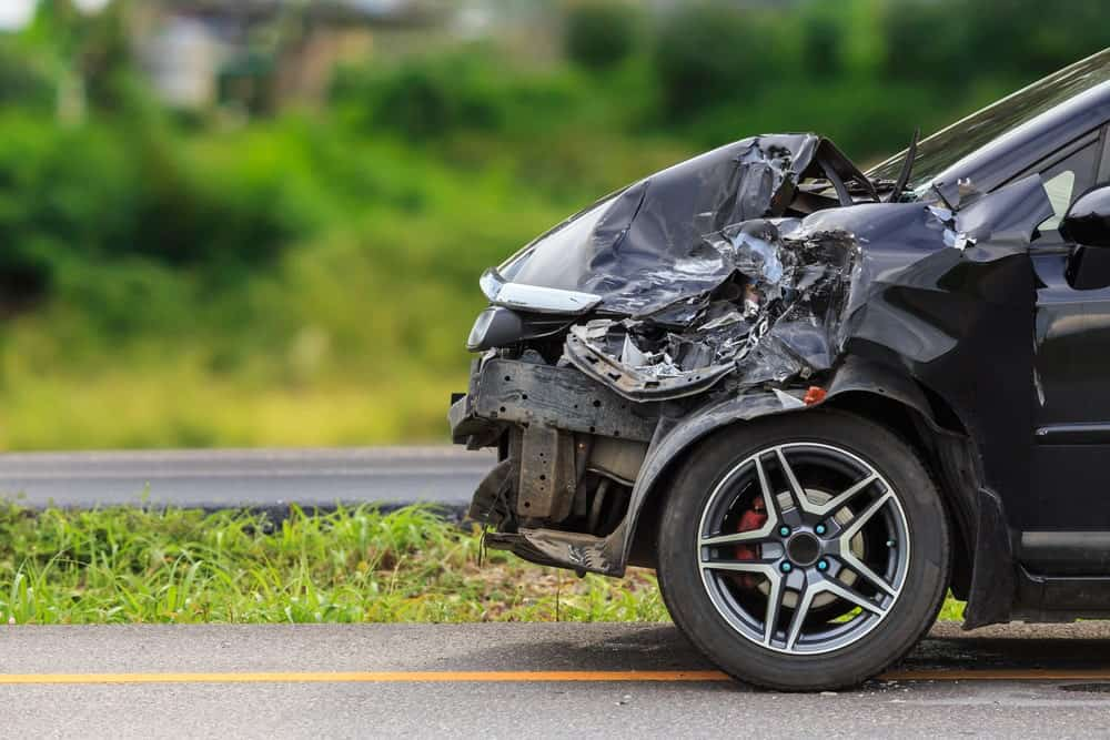 Side-view of a black car damaged in an accident
