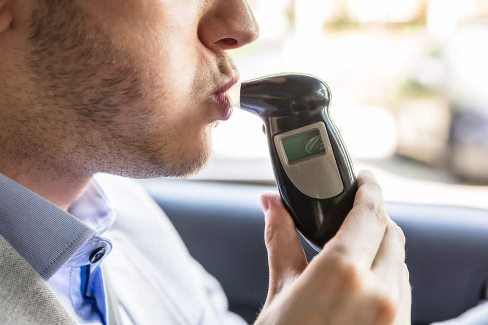 Person in a car using Breathalyzer