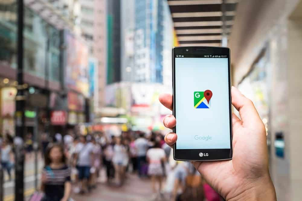 Hand holding a mobile phone showing a Google map logo onscreen.
