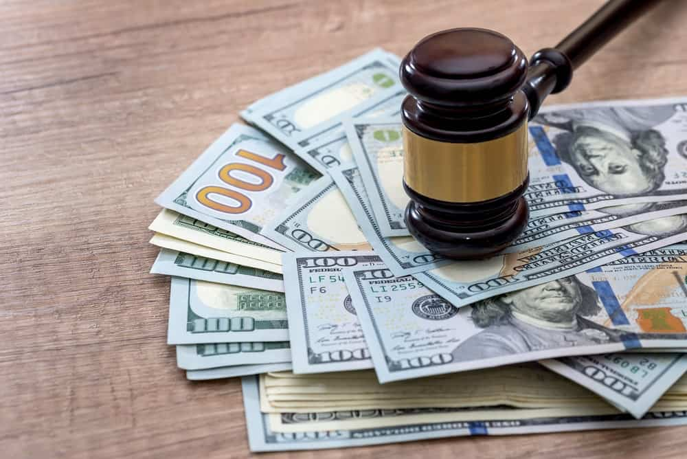 Hundred dollar bills under a gavel on a table.