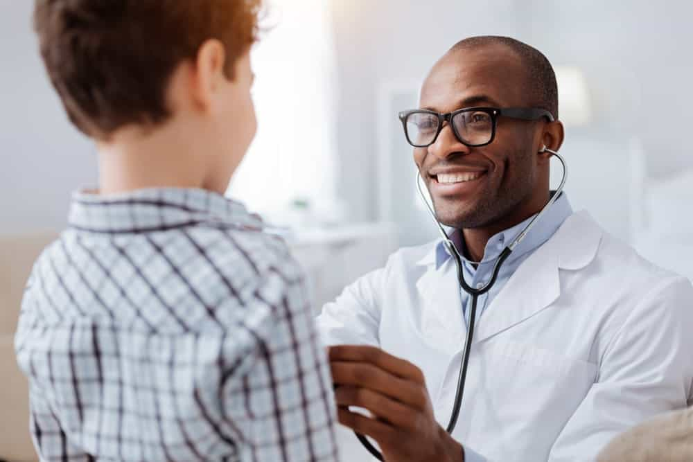 A cheerful male doctor using his stethoscope on a young boy