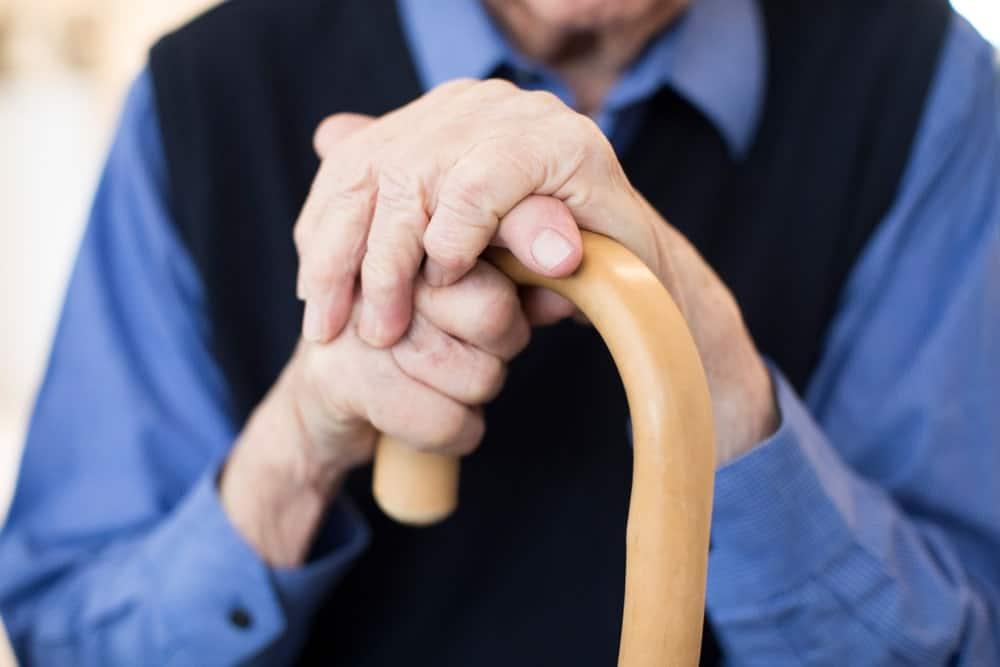 Closeup of an elderly person's hands holding a walking crane.