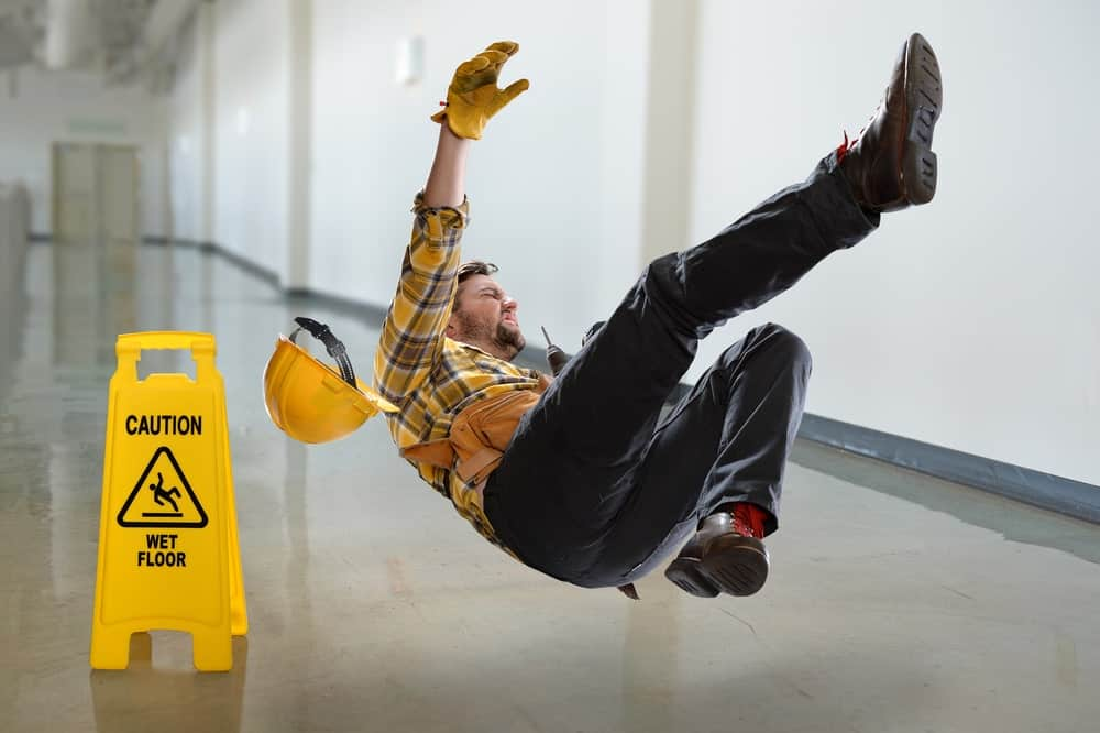 A construction worker slips on a wet floor.