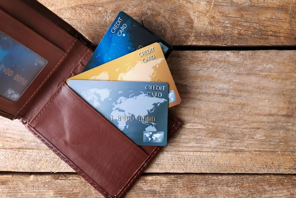 A trio of various credit cards sticking out a brown wallet on a wooden desk.