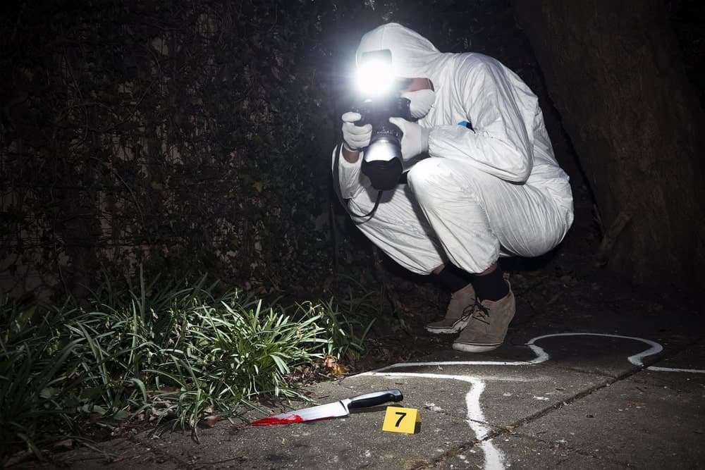 A forensic photographer with a camera