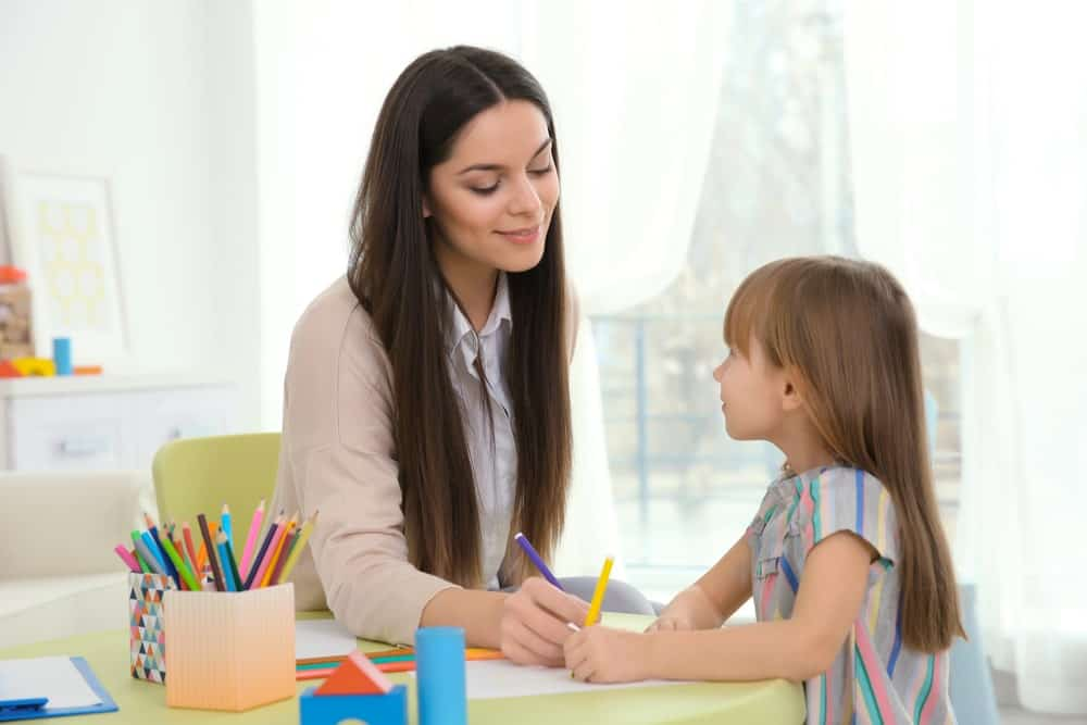 A social worker working with a young girl at school
