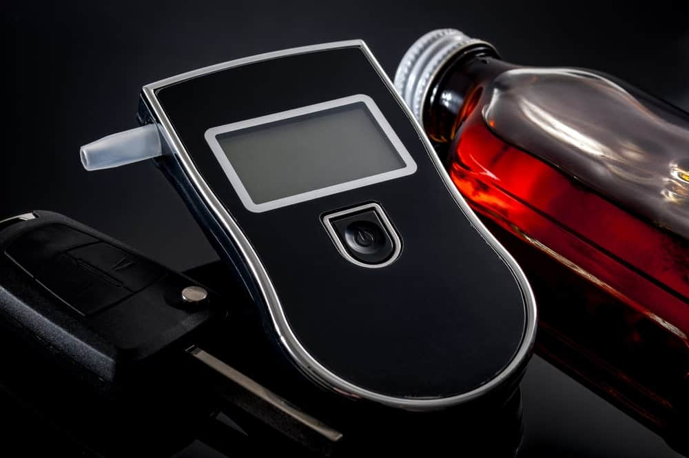 A breathalyzer between a car key and a bottle of an alcoholic drink on black background.