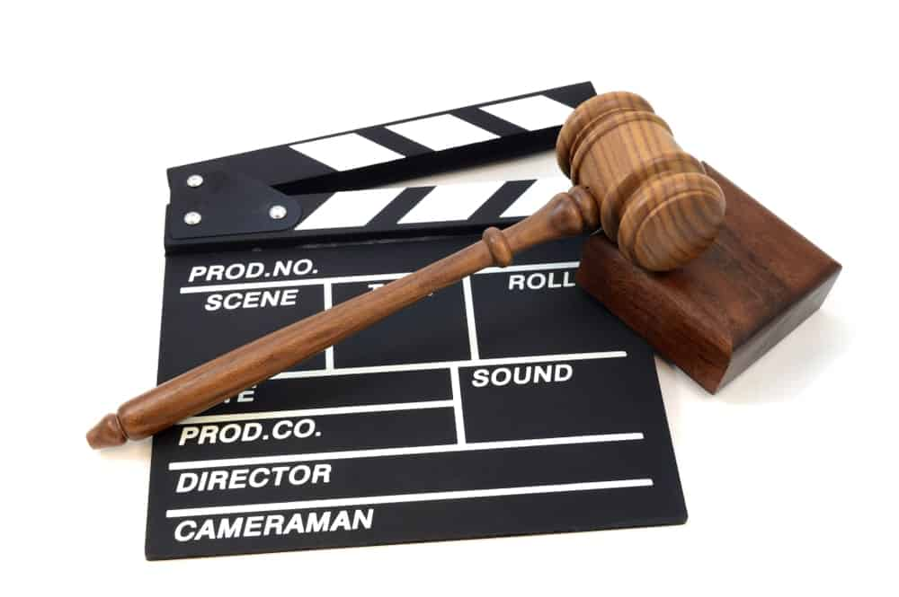 Judge's gavel on a movie clapboard.