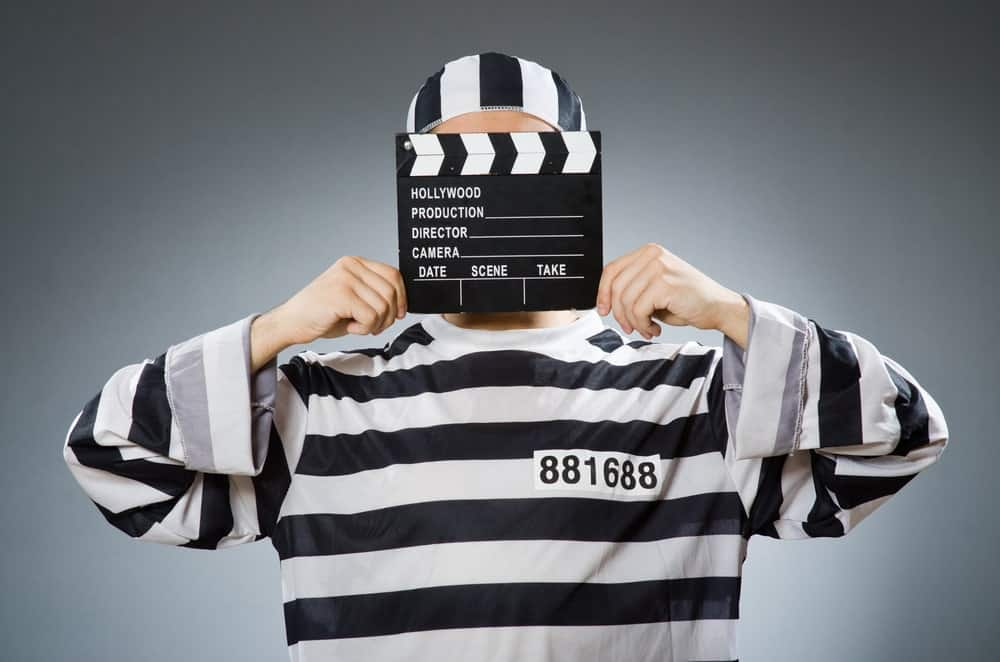 Inmate holding a movie clapper.